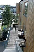 Trappen er flyttet ut på baksiden for å spare areal. Dessuten er den utformet slik at hver etasje får en terrasse.