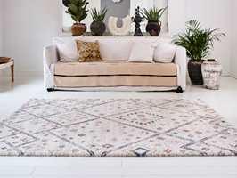 Det sandfargede teppet i sofaen, gulvteppet med lubben luv og rolig mønster, samt grønne planter gir den hvite stuen en hyggelig og innbydende atmosfære.