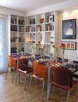 Spisebordet av frostet glass er omkranset av bokhyller. Som det står her er det plass til 5 personer. Bordet kan trekkes ut til dobbel størrelse, enten det er fest eller det trengs større plass å jobbe på. Gjennomskinnelige materialer som glass og pleksi er lurt å benytte i små værelser, det tar visuelt minimalt med plass. Hyllene har Tobiassen bygget selv av MDF-plater. De er ikke dypere enn høyst nødvendig for å få plass til bøker. I forkant er det satt på en liten list, da ser det hele litt mer forseggjort ut. Herfra ser vi inn i kjøkkenet.