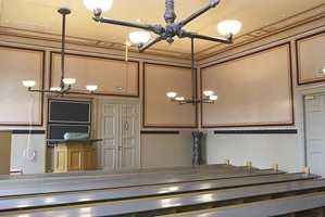 Fra et av auditoriene. Den gamle tavlen, støpejernovnen og knaggrekken er beholdt. Lampene er opprinnelig gasslykter.