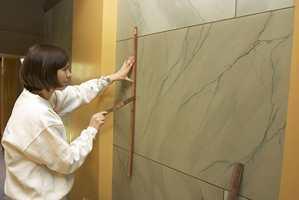 De marmorerte veggene i inngangspartiet måtte males på nytt da utgangspunktet var for dårlig. Her er Mona Øvstebø fra Klaveness & Bratfoss i sving.