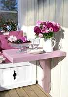 Et lite, snertent bord, malt i rosa. Det kan slås ned når det ikke er i bruk.