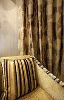 Møbelstoffene fra Harlequin matcher her gardiner og tapet, gardinene trendriktige med store mønstre.
