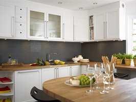 Etter: Kjøkkeninnredningen ble malt hvit og dørknottene ble byttet ut med moderne dørhåndtak i stål. I tillegg ble de oransje flisene over benkeplaten byttet ut med grå mosaikkfliser i samme farge som gulvet.