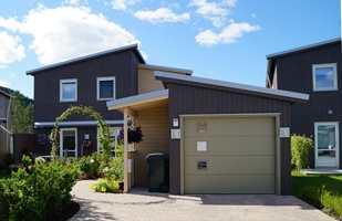 Moderne bebyggelse i mørke farger, med grågrønn garasjeport.