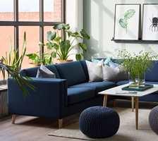 <b>HUSK PLANTENE:</b> Nå tar vi naturen inn i stuen, og innreder med grønne planter. Men planter må også rengjøres. Veggen er malt med fargen Nordisk grønn fra Nordsjö og den blå sofaen er fra Bohus. (Foto: Bohus)