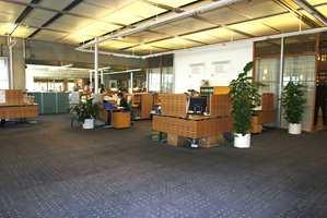 Stort kontorlandskap lagt med tepper i hele lokalets lengde.