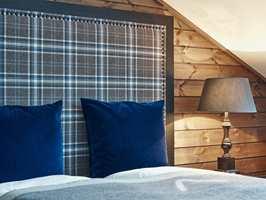 <b>HYTTEKOS:</b> Lune farger og myke materialer som beiset panel, ull og rutemønster gir assosiasjoner til tradisjoner, norsk hverdagsliv og hyttekos. Her kan man være seg selv, sammen med andre.
