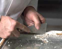 Små rester av kitt, maling og gamle stifter fjernes med sylskarp spesialskrape i metall.