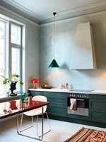 <b>HARMONI:</b> Vinduene på kjøkkenet er malt i samme duse nyanser av blågrønt som veggene. Med kjøkkenfronter i en mørkere nyanse av samme farge og en liten rød kontrast er dette en enkel palett som skaper et rolig rom. (Foto: Pure & Original Paint)