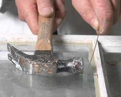 Stift kan du få i stenger på 20-30 centimeters lengder. Knekk stifttråden i rett vinkel og bank inn. Slå litt oppover med hammeren, så du ikke treffer glasset for hardt.