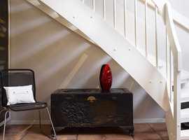 En gammel, kinesisk kiste i godt selskap med en moderne stol, i lyse, delikate omgivelser. Kisten brukes til oppbevaring av votter, luer og skjerf.