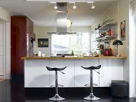 Kjøkkenet sett fra stuen; lyst, åpent og inkluderende.