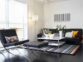 Sofaen ble som ny med hvit bakgrunn og sort gulv! Teppe og puter står for fargeinnslagene.